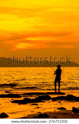 Silhouettes of fishing by the sea in the evening - stock photo