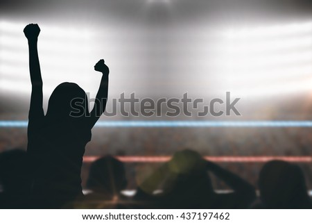 Silhouettes of football supporters against focus on foreground of ropes in a boxing ring - stock photo