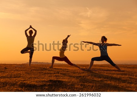 Silhouettes of girls practicing yoga in sunset - stock photo
