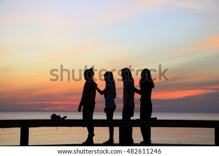 Silhouettes of group of teen on the beach