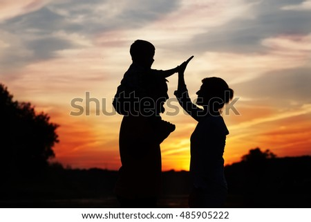 Silhouettes of  happy childn with mother and father. Family at sunset, summertime