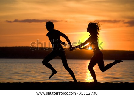 Silhouettes of happy couple having fun on seashore at sunset - stock photo