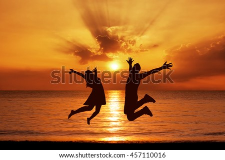 Silhouettes of happy couple jumping on background of sea at sunset - stock photo