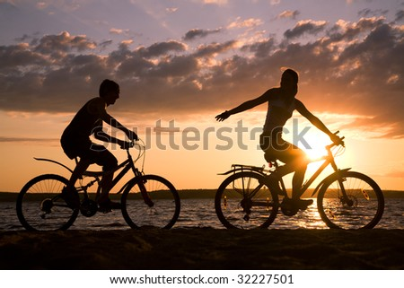 Silhouettes of happy couple riding their bicycles on seashore at sunset - stock photo