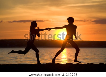 Silhouettes of happy couple running down seashore at sunset - stock photo