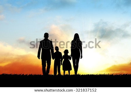 Silhouettes of happy family during sunset time - stock photo
