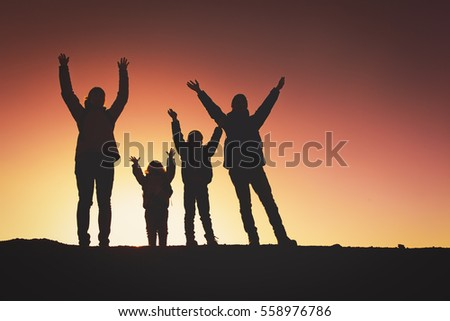 Silhouettes Of Happy Family With Two Kids Hiking At Sunset