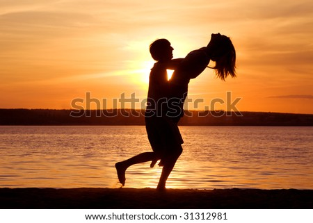 Silhouettes of happy guy holding his girlfriend and having fun at sunset - stock photo
