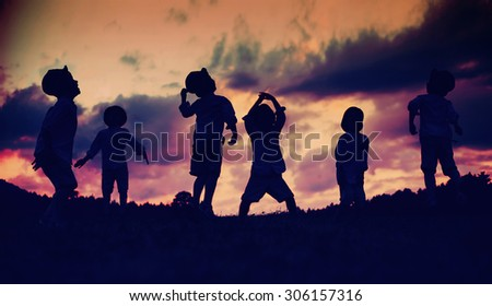 Silhouettes of happy kids playing on meadow at sunset - stock photo