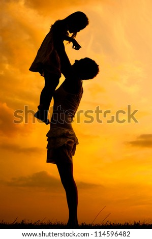 Silhouettes of happy mother and daughter at sunset. - stock photo