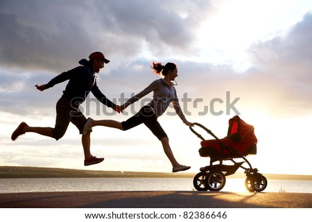 Silhouettes of happy parents are running for a pram - stock photo