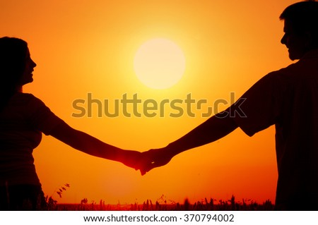 Silhouettes of happy smiling young couple in wheat field at summer sunset. - stock photo