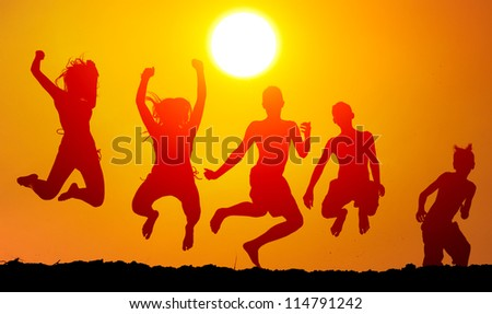 Silhouettes of happy teenagers jumping high in the air on sunny summer day. - stock photo