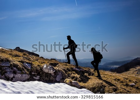 silhouettes of hikers walking in the mountains breathing clean air - stock photo