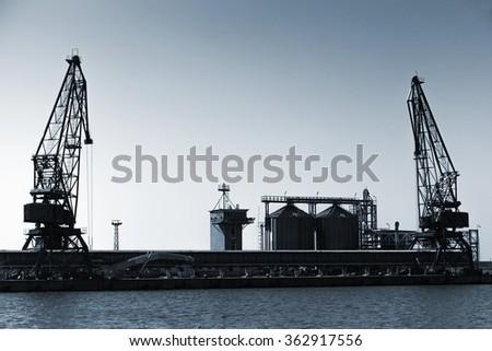 Silhouettes of industrial cranes, Balchik port, Bulgaria. Blue toned stylized photo - stock photo