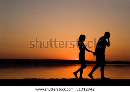 Silhouettes of man and woman holding each other by hands while walking at sunset - stock photo