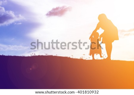 Silhouettes of mather and little daughter walking at sunset - stock photo