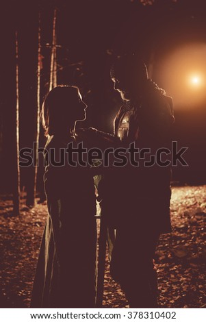 Silhouettes of medieval knight in heavy armor and his princess. Artistic toning. - stock photo