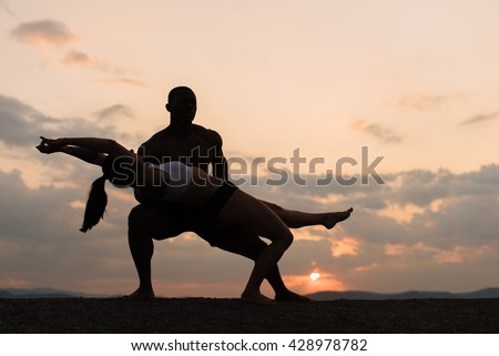 Silhouettes of mixed gymnastic couple dancing on sunset. Grace and beauty of human's body
