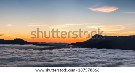 Silhouettes of mountains and clouds at sunset