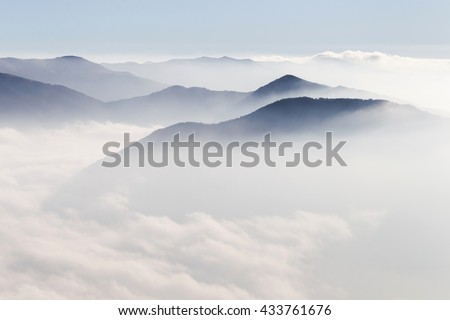 Silhouettes of mountains in the mist - stock photo