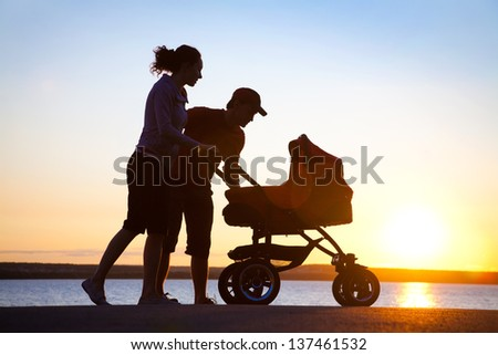 Silhouettes of parents loving  their child in a stroller - stock photo