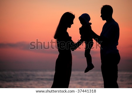 Silhouettes of parents with child on hands against  sea decline - stock photo