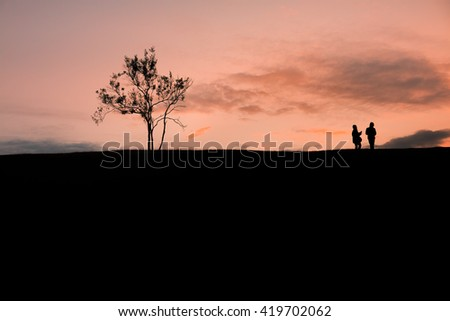 Silhouettes of people and tree on top of mountain with sunrise at samer dao mountain, Nan province, Thailand