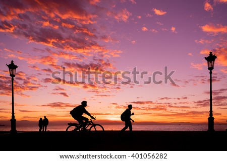 Silhouettes of people enjoying a walk by the seaside of the town during sunset - stock photo
