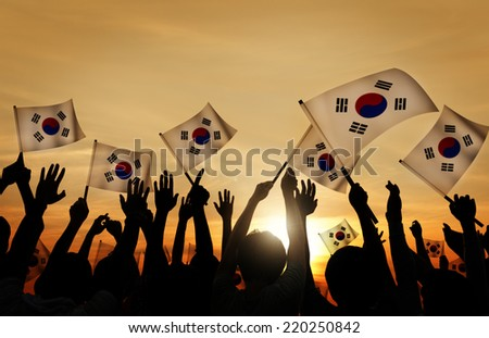 Silhouettes of People Holding Flag of South Korea - stock photo
