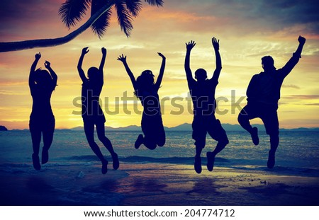 Silhouettes of People Jumping On Beach