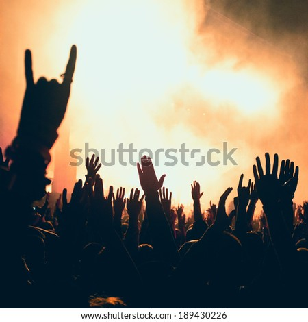 silhouettes of people on a rock concert raising hands, stage light in background. NOTE - Some noise and artefacts visible due the use of high ISO because of difficult lighting conditions  - stock photo