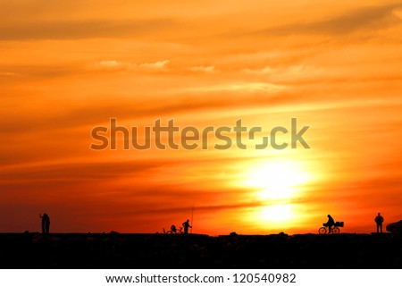 Silhouettes of people on orange sunset's background
