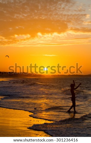 Silhouettes of people on the ocean shore at sunset in Cumbuco, Ceara, Brazil - stock photo
