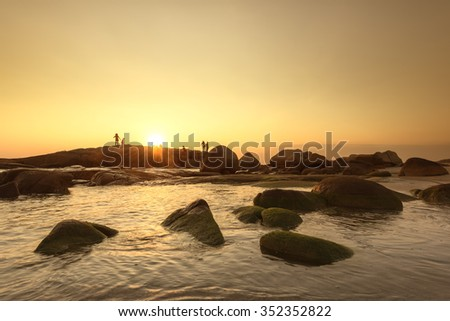 Silhouettes of people on The rock watching the sunset - stock photo