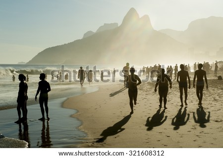 Silhouettes of people walking along golden sunset shores of Ipanema Beach Rio de Janeiro Brazil - stock photo
