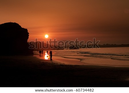 Silhouettes of people walking by a beach at sunset. - stock photo