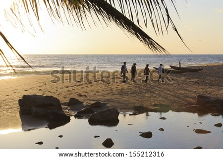 Silhouettes of people walking down the beach in the evening sun - landscape, in Axim, Ghana - stock photo