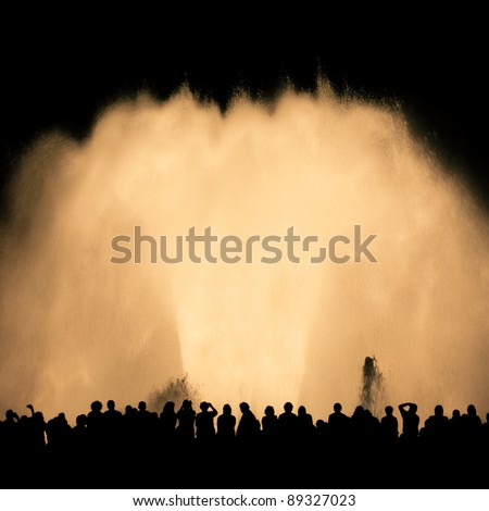 Silhouettes of people watching Montjuic's fountain show - stock photo