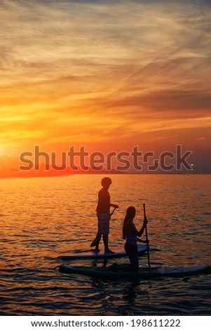 Silhouettes of perfect couple engage standup paddle boarding and meets dawn in the Gulf of Indian Ocean, the perfect orange sunset over the ocean