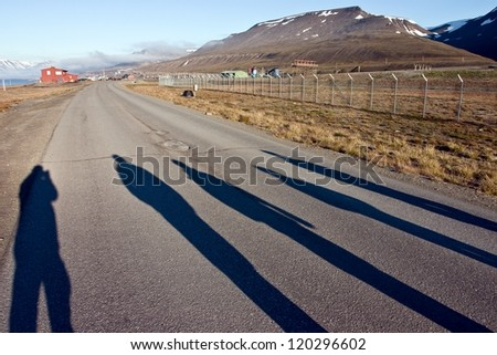 Silhouettes of Persons Walking on the Road. This Photo Was Taken on the Svalbard Archipelago in the Arctic in the Summer. - stock photo