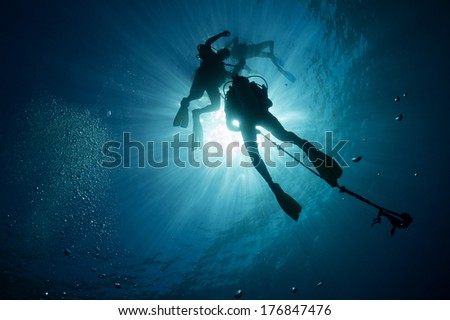 Silhouettes of scuba divers descending on a descent line with the sun behind them - Akumal, Riviera Maya, Mexico - stock photo
