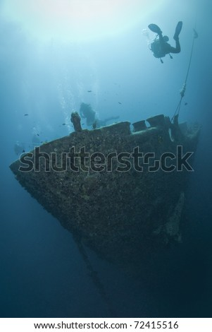 Silhouettes of scuba divers exploring the bow of the SS Thistlegorm shipwreck. SS Thistlegorm, Straights of Gubal, Red Sea, Egypt. - stock photo