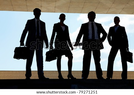 Silhouettes of several business partners standing in row outside
