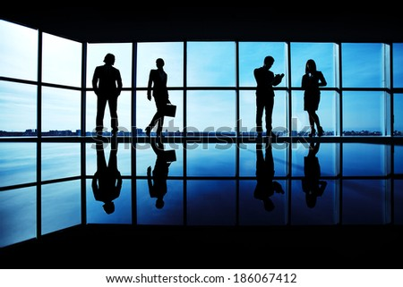 Silhouettes of several office workers standing on background of window - stock photo