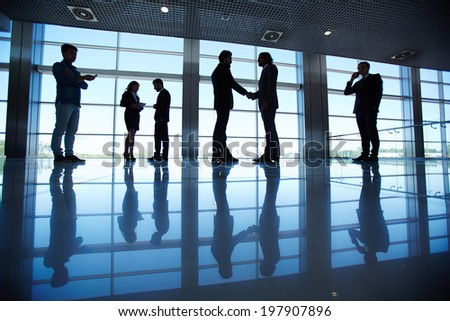 Silhouettes of several office workers working in office - stock photo