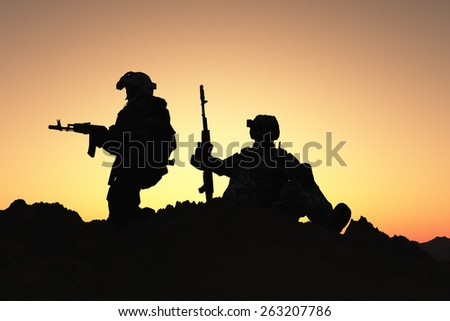 Silhouettes of soldiers against the sky.