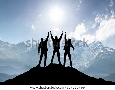 Silhouettes of team on mountain peak. Sport and active life concept