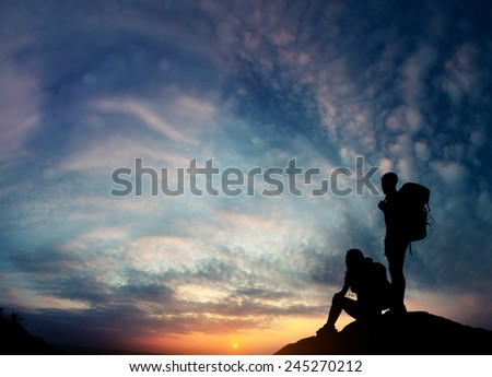 Silhouettes of the hikers relaxing on top of the rock and enjoying sunset - stock photo