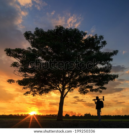 Silhouettes of the photographer and tree. Beautiful sunset sky